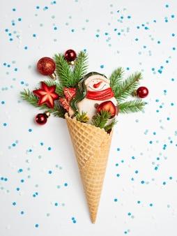 Bałwan, gałązki jodły i świąteczne zabawki w rożku waflowym. szara ściana z niebiesko-białymi płatkami śniegu. oryginalny słodki prezent.