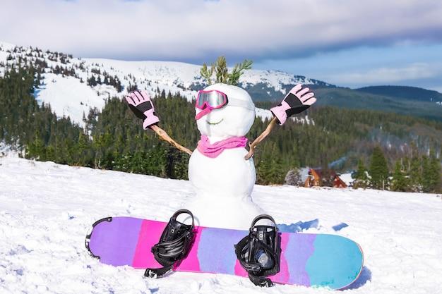 Bałwan ze snowboardem w ośrodku narciarskim w słoneczny dzień. ferie zimowe