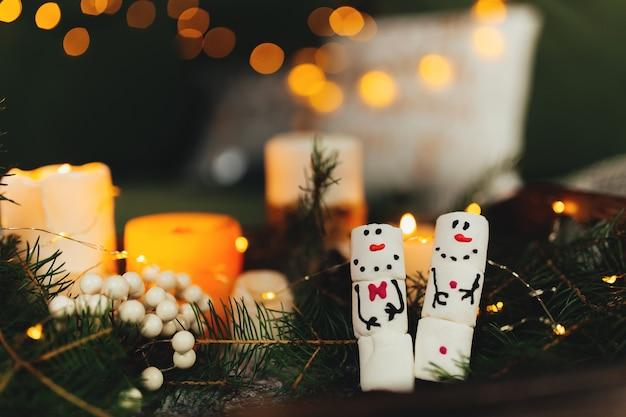 Bałwany z pianki, lampki bokeh, dekoracje świąteczne, świece.