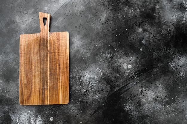 Bambusowa deska do krojenia ustawiona na pustą dla miejsca kopiowania tekstu lub jedzenia, widok z góry płasko leżący, na czarnym ciemnym tle kamiennego stołu