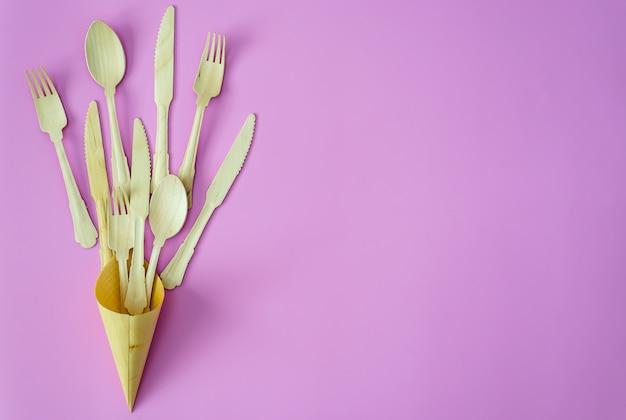 Bambusowa łyżka i widelec z rzędu na różowym lub fioletowym tle