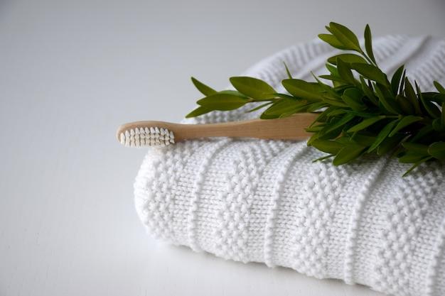Bambusowa szczoteczka do zębów na białym ręczniku i zielonych liściach