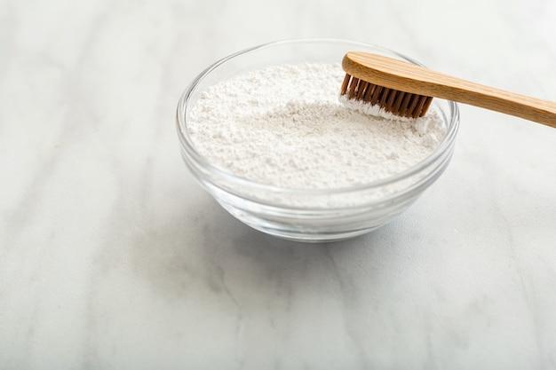 Bambusowa szczoteczka do zębów, proszek do czyszczenia zębów na tle białego marmuru. biodegradowalna naturalna bambusowa szczoteczka do zębów.