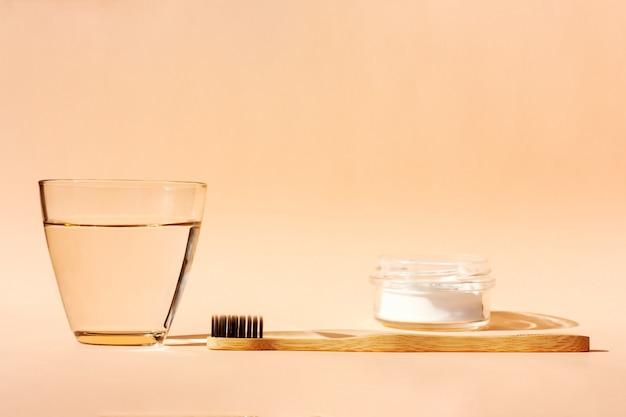 Bambusowa szczoteczka do zębów, szklanka wody i pasta w proszku na pomarańczowo