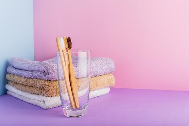 Bambusowa szczoteczka do zębów ze szkła w pastelowych, bawełnianych ręcznikach. koncepcja hygiene textile