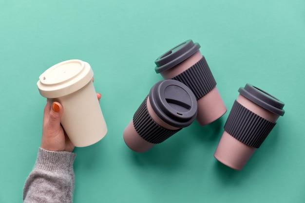 Bambusowe filiżanki do kawy, trzymaj filiżanki lub kubki podróżne w kobiecej dłoni na niebieskiej miętowej ścianie. twórczy układ płaski, obraz z góry. modna koncepcja zero odpadów, kilka ekologicznych kubków podróżnych.