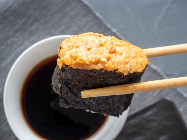 Bambusowe kije trzymają ostry gunkan. w tle jest miska sosu sojowego. ścieśniać. tradycyjna kuchnia japońska