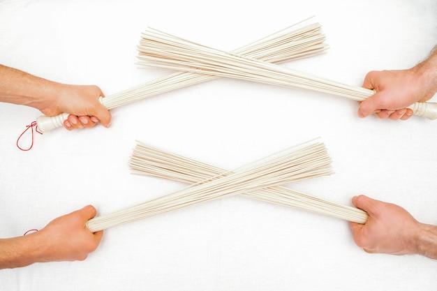 Bambusowe miotły do masażu w rękach dwóch masażystów na białym tle na białej ścianie