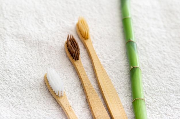 Bambusowe szczoteczki do zębów, bambusowa roślina na białym ręczniku. naturalne produkty do pielęgnacji zębów do kąpieli.