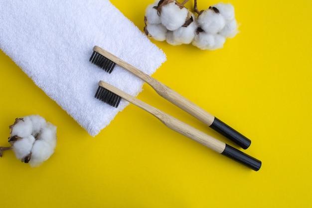 Bambusowe szczoteczki do zębów i biały ręcznik na żółtym tle