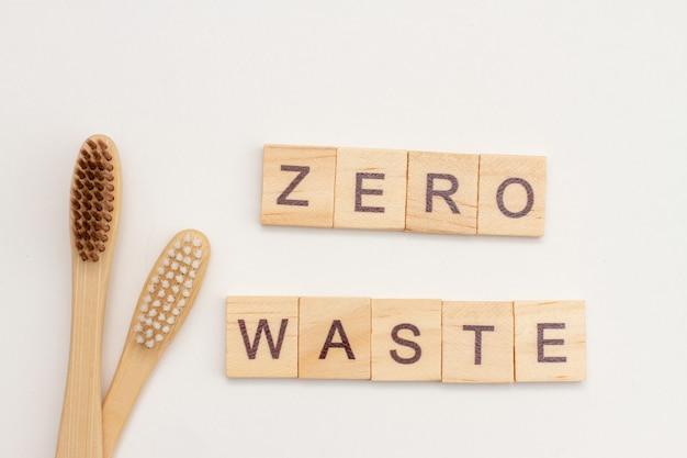 Bambusowe szczoteczki do zębów i napis zero waste wykonane z drewnianych kostek na białym tle. koncepcja przyjazna dla środowiska