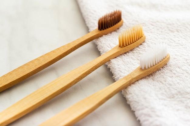 Bambusowe szczoteczki do zębów na białym ręczniku na marmurowym stole. naturalne produkty do kąpieli.
