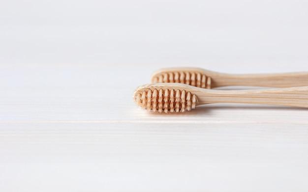 Bambusowe szczoteczki do zębów na białym tle stołu, minimalna koncepcja przyjazna dla środowiska i zrównoważonego rozwoju