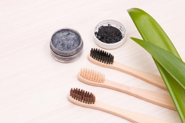 Bambusowe szczoteczki do zębów na drewnianym stole, domowa pasta do zębów z węglem drzewnym w małym szklanym słoiczku