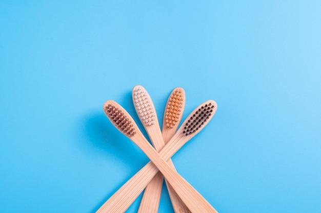Bambusowe szczoteczki do zębów na niebieskim tle. ekologiczna codzienna higiena jamy ustnej, pielęgnacja zębów i zdrowie. produkty do czyszczenia ust. koncepcja opieki stomatologicznej.
