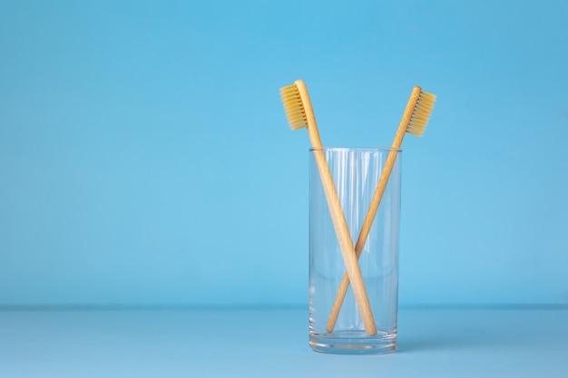 Bambusowe szczoteczki do zębów na niebieskim tle w szklance ekologiczne produkty do higieny osobistej dla ludzi