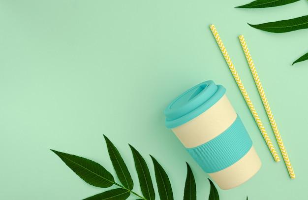 Bambusowy kubek ekologiczny z silikonowym uchwytem i papierowymi słomkami do picia na zielonym tle.