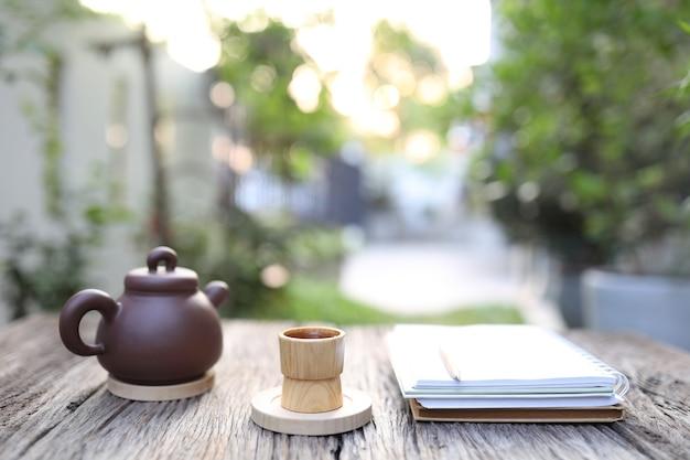 Bambusowy kubek i dzbanek do herbaty z zeszytami na drewnianym stole