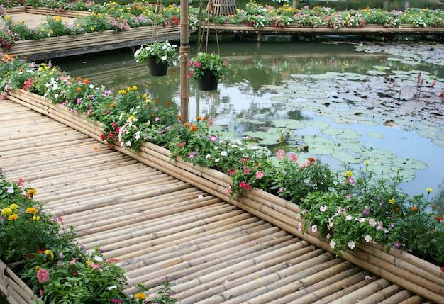 Bambusowy most z kwiatem na stawie