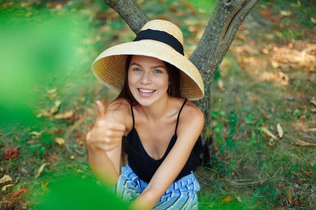 Bambusowy stożkowy kapelusz mao hainan. dziewczyna wegańska, turystyczna, siedząca pod drzewem na trawie, odpoczywająca i pokazująca klasę, ręka gest, palec w górę. szeroki śnieżnobiały uśmiech.