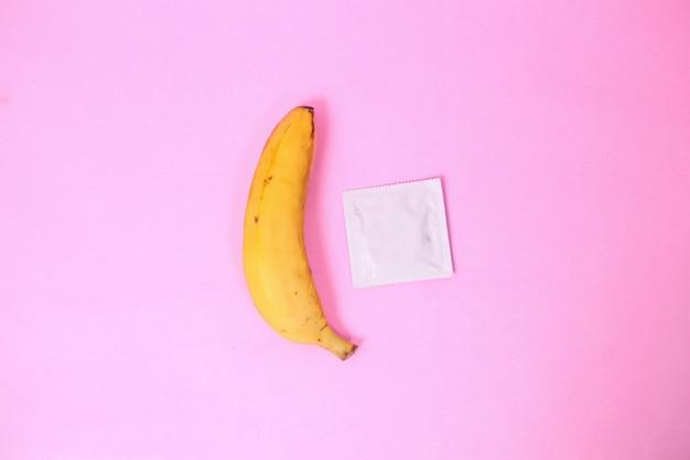 Banan i antykoncepcja na białym tle na różowym tle
