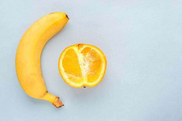 Banan I Pół Pomarańczy Na Niebieskim Tle. Koncepcja Seksu. Koncepcja Penisa I Pochwy. Premium Zdjęcia