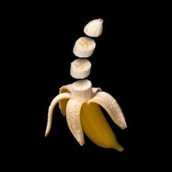 Banan na białym tle na czarnej powierzchni. surrealistyczny projekt. kawałki owoców unoszące się w powietrzu.