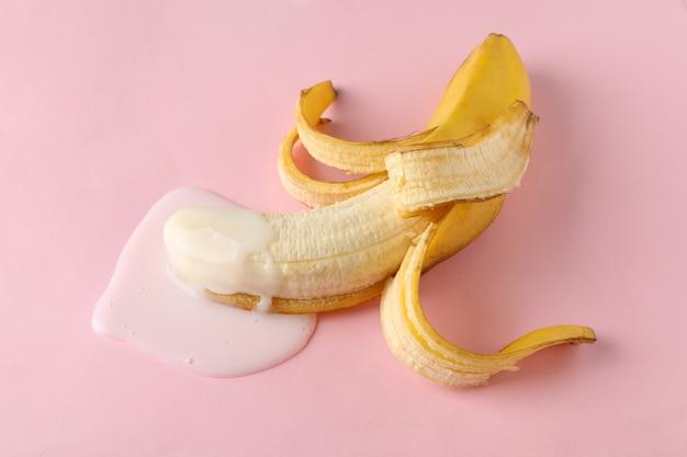 Banan na różowym stole. świeże owoce erotyczne