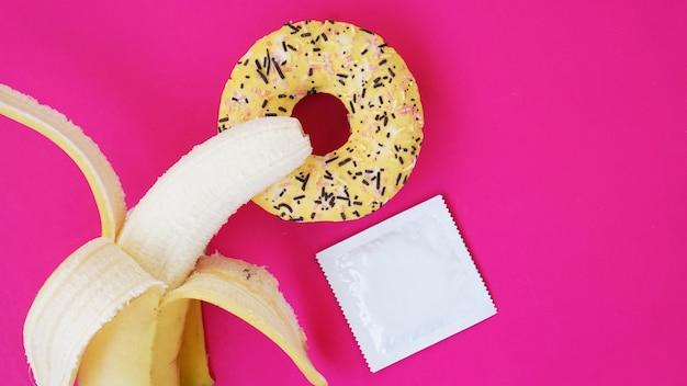 Banan, pączek i prezerwatywa. pomysł na seks. jasny obraz na różowym tle. pojęcie zdrowia i seksu chronionego