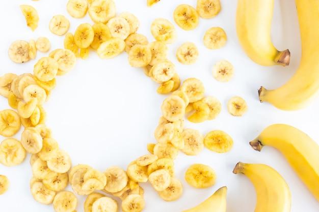 Banan z stosem wysuszeni bananowi plasterki z pustą okrąg kopii przestrzenią odizolowywającą na bielu