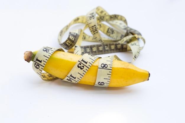 Banan zawinięty w miarkę na białym tle.