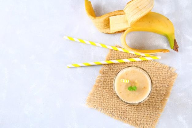 Bananowy koktajl z papierową tubą i miętą. banany są całe i pokrojone na szarym tle
