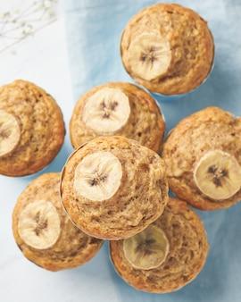 Bananowy muffin, odgórny widok, zamyka up, pionowo. rano śniadanie na niebieski serwetka, biały stół betonowy