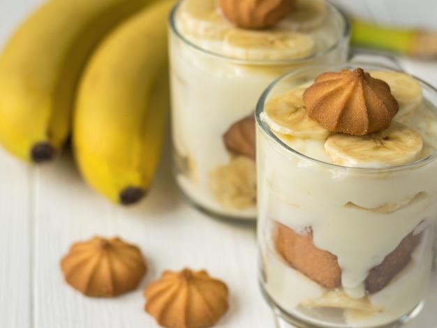 Bananowy pudding w szkłach z ciastkami na białym drewnianym stole.