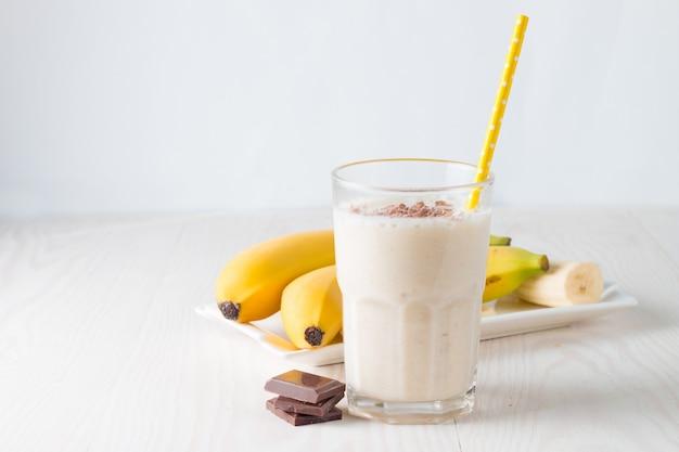 Bananowy smoothie na drewnianym stole.