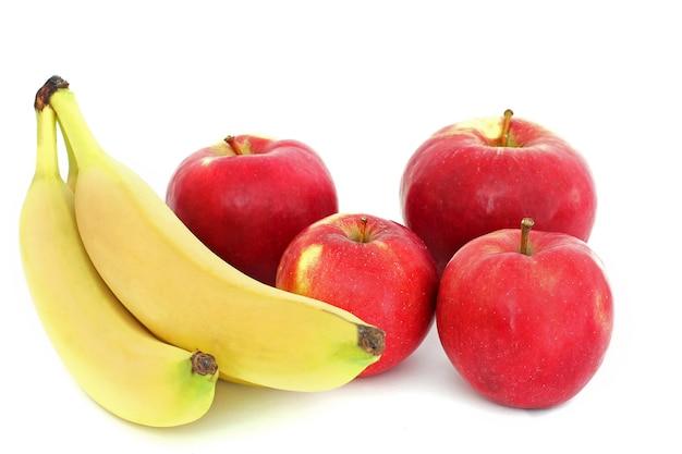Banany i jabłka na białym tle.