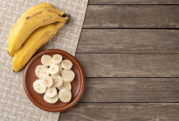 Banany i plasterki na drewnianym stole z miejsca na kopię.