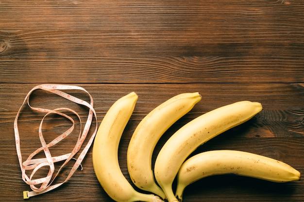 Banany i taśma pomiarowa na drewnianym stole. widok z góry, miejsce na kopię