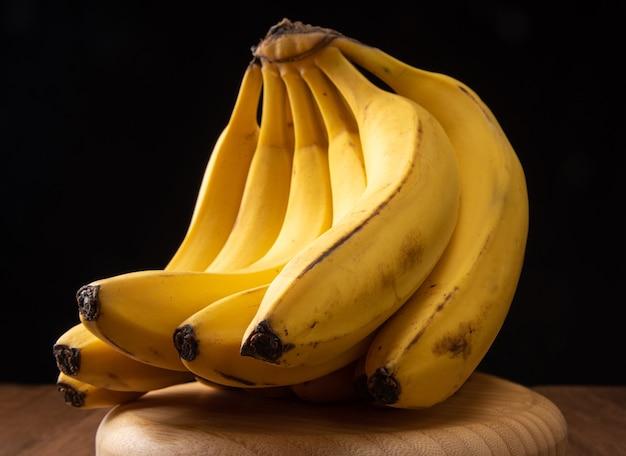 Banany, kiść bananów ułożona na okrągłej drewnianej powierzchni