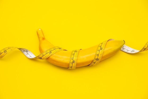 Banany mają taśmę. na żółtym tle - koncepcja diety.