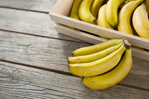 Banany w drewnianej skrzyni na drewnianym stole