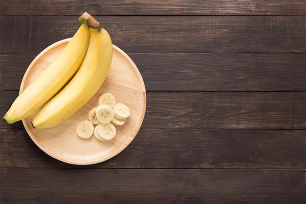 Banany w drewnianym naczyniu na drewnianym tle. miejsce na tekst