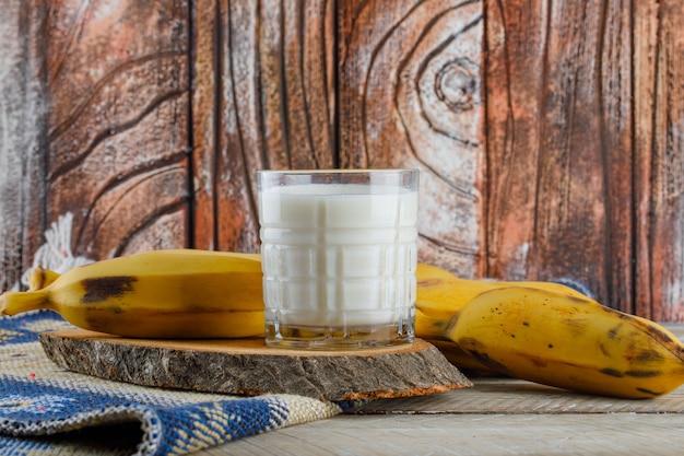 Banany z mlekiem, widok z boku deski do krojenia na dywanik drewniany i kilim