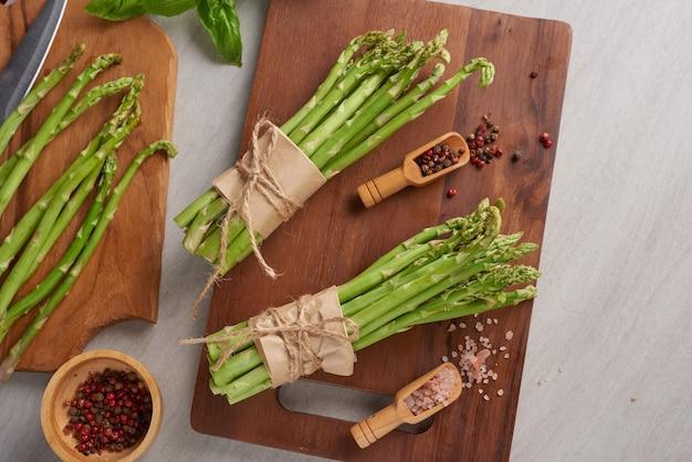 Banches świeżych zielonych szparagów na powierzchni drewnianych