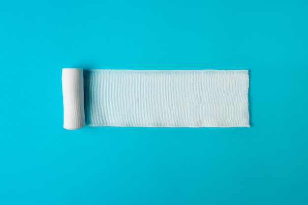 Bandaż medyczny nieskręcony na niebieskim .zdrowie. zdrowy tryb życia . pojęcie farmakologii. pojęcie leków. pojęcie instrumentów medycznych. koncepcja medycyny.