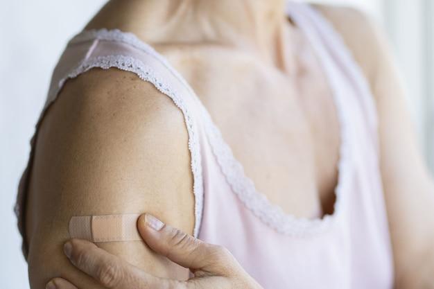 Bandaż na ramieniu kobiety obok jej dłoni