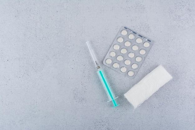 Bandaż, strzykawki i pigułki medyczne na marmurowym tle. zdjęcie wysokiej jakości