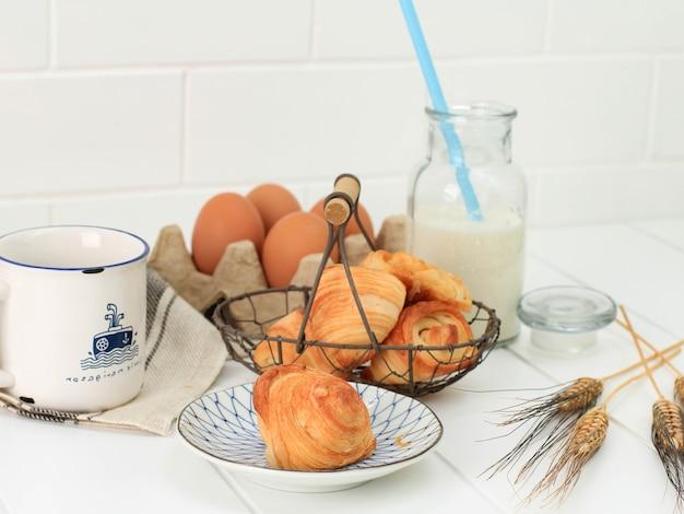 Bandung, indonezja, 10112020: mini croissant z mlekiem, flaky ciastka z masłem z francji. serwowane na talerzu i tkanym koszu drucianym na białej kuchni.