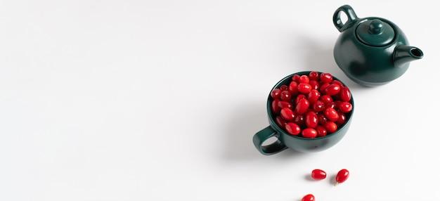 Baner, dojrzałe czerwone owoce derenia w zielonym naczyniu na białym tle