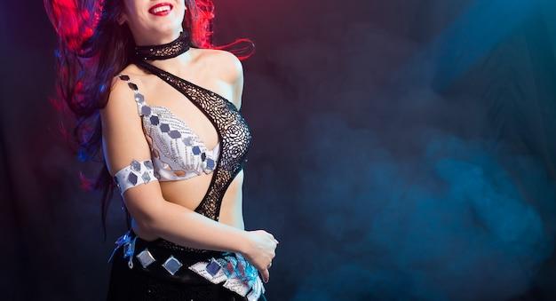 Baner dziewczyna tańczy taniec brzucha, fusion lub tribal. kobieta w pięknym stroju demonstruje w tańcu urocze i delikatne ruchy. skopiuj miejsce.